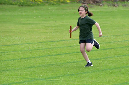 Fast and strong young girl (female age 07-08) running relay race on grass running track outdoors.