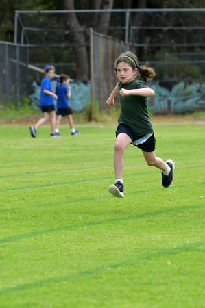 Determent young girl (female age 07-08) running relay race on grass running track outdoors. Banque d'images