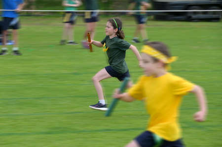 Motion blur of a strong, fast and determent young girl (female age 07-08) running relay race on grass running track outdoors.