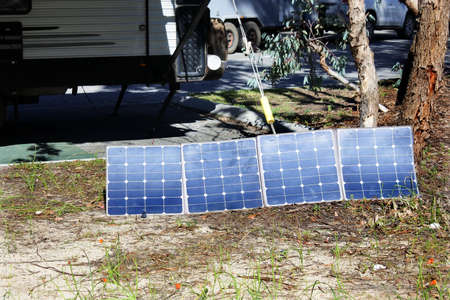 Group of solar panels charging caravan power in outdoor campground. No people. Copy space