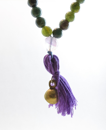 beautiful isolated jade mala with a purple tassel, praying beads