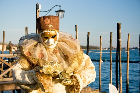 Mask posing along famous promenade in front of San Marco square, (Venice, Italy) during Venice Carnival. photo