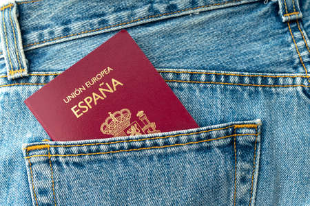 CLOSE UP OF SPANISH PASSPORT IN BLUE JEANS POCKET. TRAVELER CONCEPT.