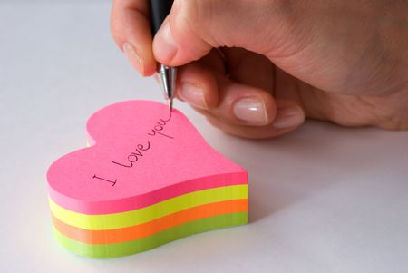 Hand with pen writing I love you on heart shaped sticky notes Stock Photo