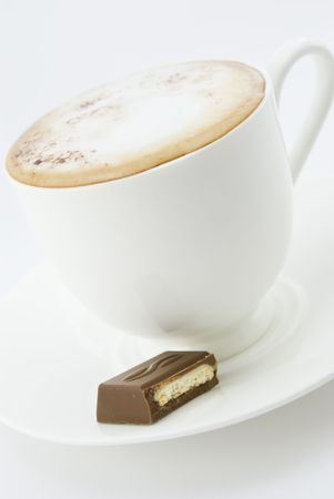 coffee hour: Cup of coffee, latte or cappuccino on a white plate with a piece of chocolate Stock Photo