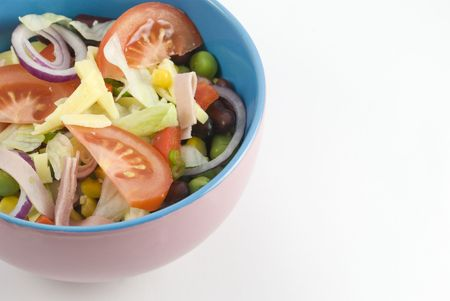 Fresh garden salad in a colorful bowl on white background photo
