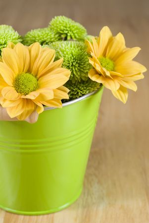 Bunch of colourful flowers arranged in little green metal bucket Stock Photo