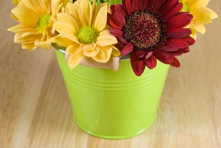 Bunch of colourful flowers arranged in little green metal bucket photo