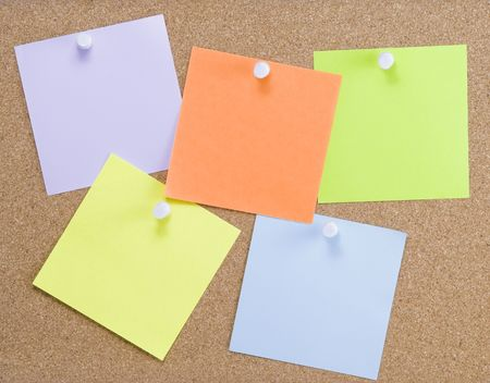 Colorful sticky notes attached to a corkboard with white thumbtacks photo