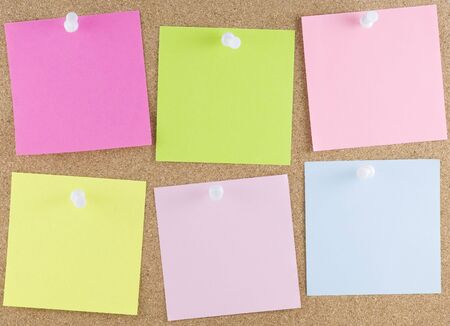 Colorful sticky notes attached to a corkboard with white thumbtacks Stock Photo