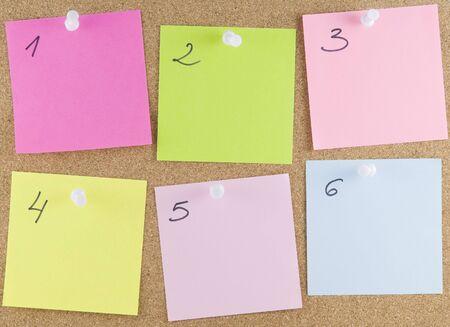 notas adhesivas: Coloridas notas adhesivas adjunta a una corkboard con tachuelas blancos