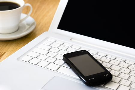 White laptop, black cell phone and cup of coffee arranged on wooden table Stock Photo - 5490116