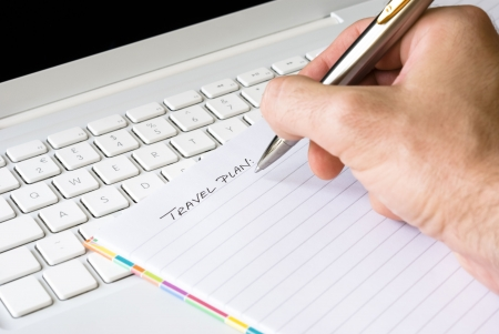 Hand writing travel plan with silver pen arranged on white laptop keyboard  Stock Photo - 5490122