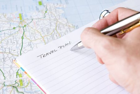 Hand writing travel plan in a lined spiral notepad arranged on a map photo