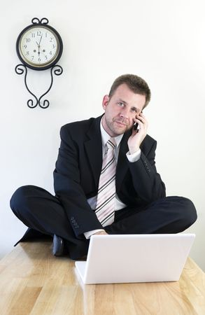 Young businessman working with laptop and cell phone photo