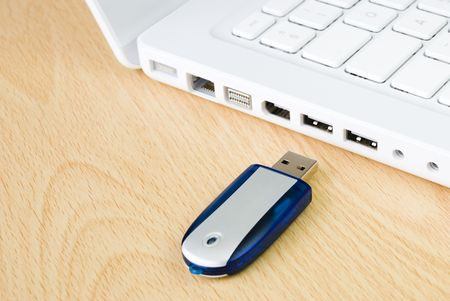ラップトップとフラッシュのペンドライブの木製のテーブル上に配置 写真素材