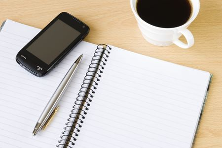 Cell phone with spiral notebook and cup of coffee arranged on office table