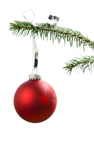 Red Christmas tree bauble hanging on pine tree branch isolated on white background Stock Photo