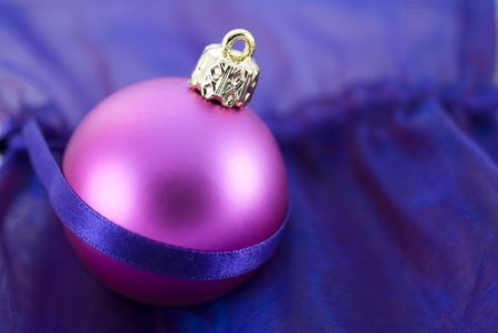 Christmas tree ball arranged with decorative purple fabric background photo