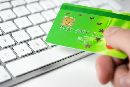 Hand holding credit card with white computer keyboard in background photo