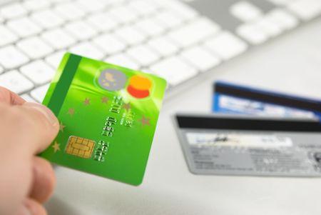 バック グラウンドで白いコンピューターのキーボードとクレジット カードを持っている手