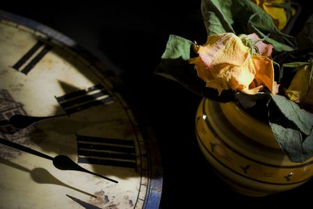 Dried rose bouquet arranged with vintage clock. Passing time concept. photo