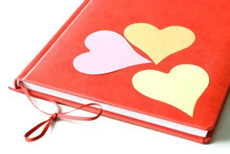 Drie hart gevormde kleverige nota's sticked aan rode agenda die op witte achtergrond wordt geïsoleerd. Valentijnsdag en liefde concept.