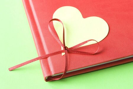 Heart shaped sticky note attached to red diary on a green background. Love concept.