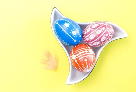 Colorful handmade Easter eggs in saucer with color feathers isolated on yellow background photo