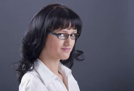 Beautiful dark-haired secretary studio shot against grey background. photo