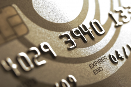 swipe: Details of a gold credit card with chip and some numbers, shallow DOF