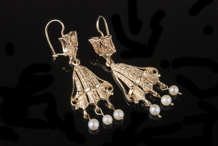 Golden earrings with pearls reflected on black background photo