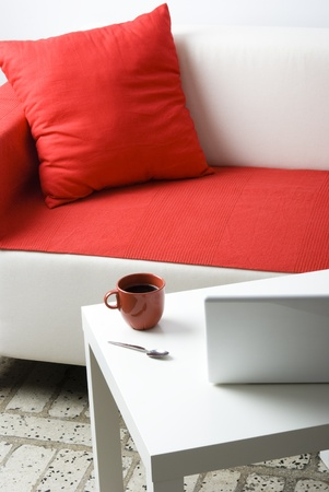 red sofa: Room interior with laptop and coffee cup