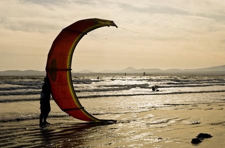 カイトサーファーは海辺で彼の凧を保持