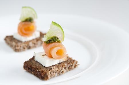 salmon ahumado: Morena de salmón aperitivo con queso feta, cal y pesto