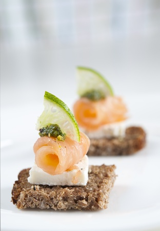 Brown bread salmon appetizer with feta cheese, lime and pesto Stock Photo - 13614999