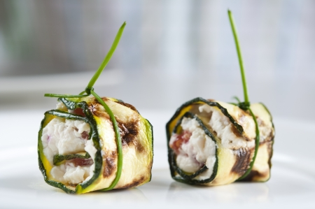 Two zucchini appetizers stuffed with ricotta cheese and tomato