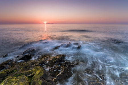 Irish sunrise over rocky coastline