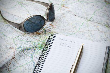 Reisplan concept met notebook, schrijven, zonnebrillen, kaart en balpen