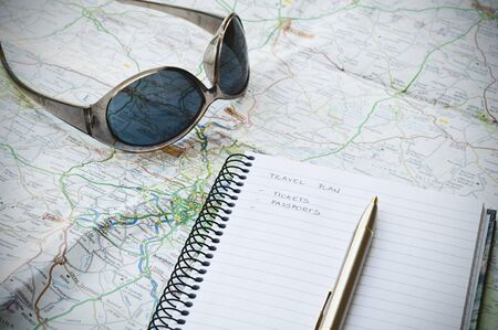 Travel plan concept with notebook, writing, sunglasses, map and ballpoint pen Stock Photo
