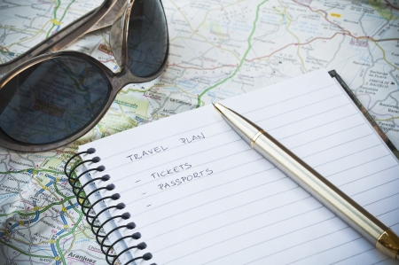 organising: Travel plan concept with notebook, writing, sunglasses, map and ballpoint pen Stock Photo