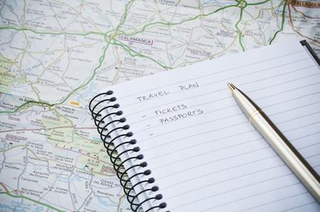 Reis planconcept met een notebook, schrijven, kaart en balpen