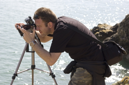 taking photograph: Amateur photographer taking pictures with DSLR camera and tripod