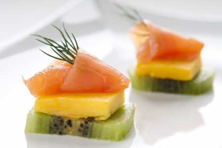 Smoked salmon appetizer with mango, kiwi and dill Imagens