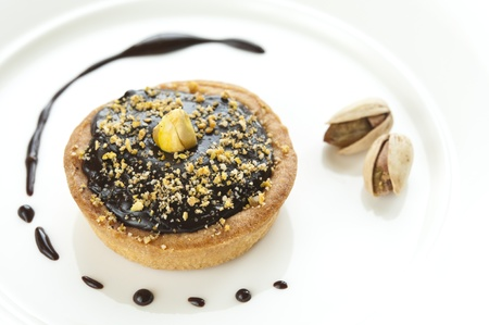Mini chocolate tart with pistachio on top