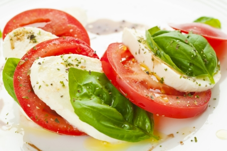 Caprese salad with mozzarella, tomato, basil and balsamic vinegar arranged on white plate
