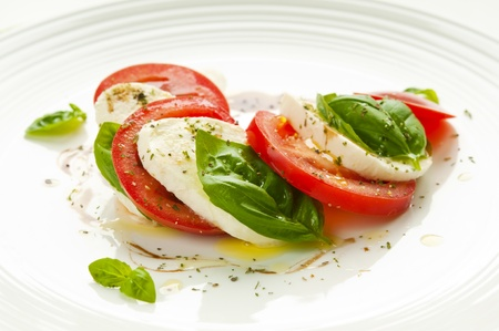 Caprese salad with mozzarella, tomato, basil and balsamic vinegar arranged on white plate