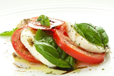 Caprese salad with mozzarella, tomato, basil and balsamic vinegar arranged on white plate photo