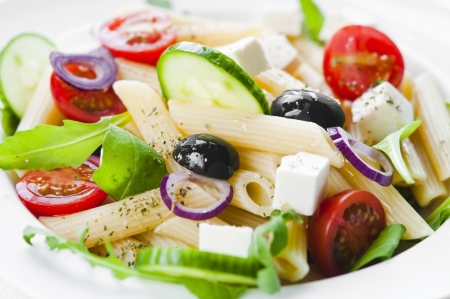 Pasta salad with tomato, black olives, arugula and feta cheese