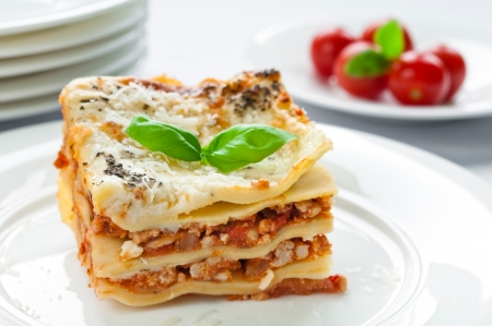 Portion of lasagna with meat topped with parmesan Foto de archivo